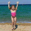 Happy young girl jumping on the beach — Stock Photo