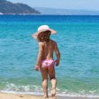 Little girl with straw hat walking on beach — Stock Photo #6160413
