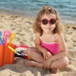 Little girl with sunglasses sitting on beach - Stock Photo
