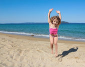 Happy little girl jumping on the beach — Stock Photo