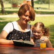 Mother and daughter reading a book — Stock Photo #6373310