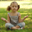 Little girl meditating in park - Stok fotoğraf