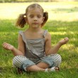 Little girl meditating in park - Stock Photo