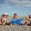 Three children playing in sand - Stock Photo