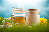 Healthy food - jars of honey and spring flowers — Stock Photo
