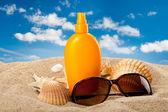средства для загара нефти и темные очки на пляже — Стоковое фото