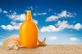 Summer holiday - suntan oil on beach — Stock Photo