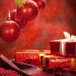 Christmas gifts and red baubles - Stock Photo