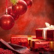Christmas gifts and red baubles — Stock Photo