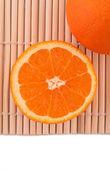 Ripe orange and half of orange on bamboo mat — Stock Photo