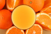 Orange juice and ripe oranges on background — Stock Photo
