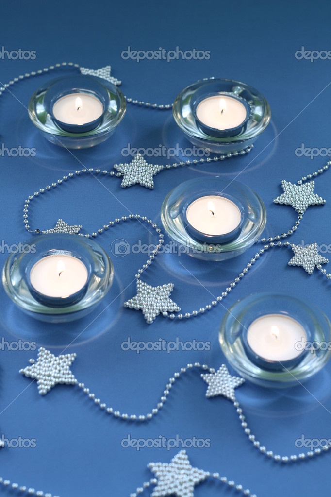 Candle lights and silver chain on blue background — Stock Photo #6575877