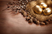 Easter - golden eggs and catkin — Stock Photo