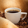 Coffee cup and beans on jute background — Stock Photo