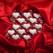 Royalty-Free Stock Photo: Valentine background - white hearts on red satin