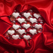 Valentine background - white hearts on red satin — Stock Photo