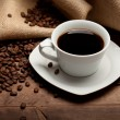 Cup of coffee and beans on jute background — Stock Photo