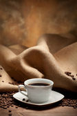 Cafe - black espresso and coffee beans — Stock Photo