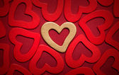 Golden heart on red hearts background — Stock Photo