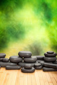 Massage stones on green background — Stock Photo