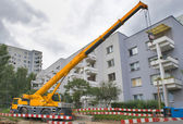 Yellow automobile crane with risen telescopic boom — Stock Photo