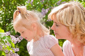 Little girl with mother sniffing lilacs — Stock Photo