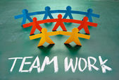 Teamwork words and colorful paper dolls — Stock Photo