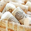 Decorative wine corks in wicker basket — Stock Photo