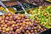 Olives, pickles and salads on market stand — Stock Photo