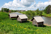 "Russian wooden houses at a river bank. Huts on ""chicken legs"". — Stock Photo"