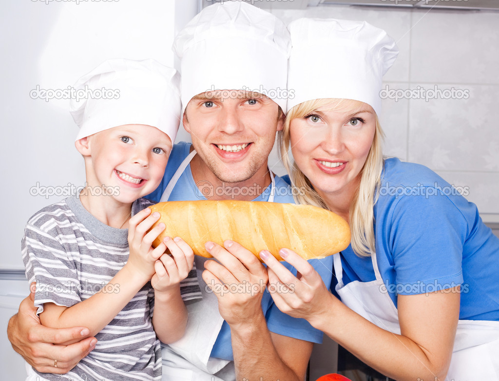 Young family; father, mother and their five year old son eating bread together in the kitchen at home — Stock Photo #6587606