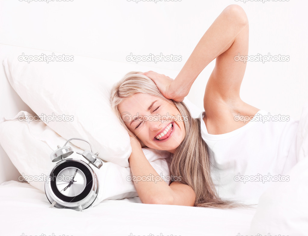 Displeased  young blond woman waking up and switching off the alarm clock    Stock Photo #6597856