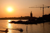 Industrial harbor at sunset and a crane — Stock Photo