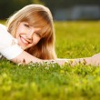 Beautiful blond girl on a grass — Stock Photo