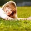 Beautiful blond girl on a grass — Stock Photo
