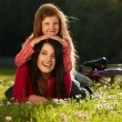 Mother and daughter on a grass - Stock Photo