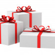 Three white gift boxes with red ribbons and bows isolated on white — Stock Photo