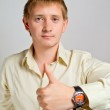 The young man has lifted the big finger on the left hand — Stock Photo