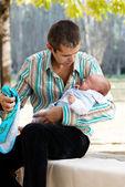 Problemas cotidianos. el padre con el hijo recién nacido en el parque — Foto de Stock