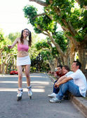 The girl on rollers under exulting barrackings of guys — Stock Photo