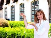 De vrouw met sleutels in een hand tegen het huis is jong — Stockfoto