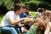 Groep studenten zitten in park op een gras — Stockfoto