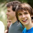 Portrait young happy teenage boy at the park with friends — Stock Photo