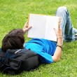 Guy laying on the grass and reading a book — Stock Photo
