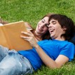 Couple students laying on the grass and reading a book — ストック写真