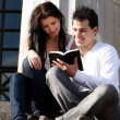 Stock Photo: Young couple of students with the book