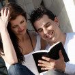 Young couple of students with the book — Stock Photo