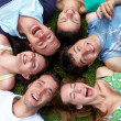 Young guys and girls lying on grass looking up — Stock Photo