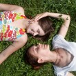 Happy mother with the daughter laying on a grass in park — Stock Photo