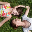 Happy mother with the daughter laying on a grass in park — Stock Photo #6379112